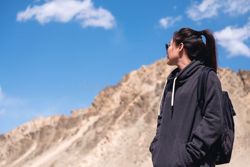 Ett turist- stående för härlig asiatisk kvinna framme av bakgrund för berg och för blå himmel arkivbilder