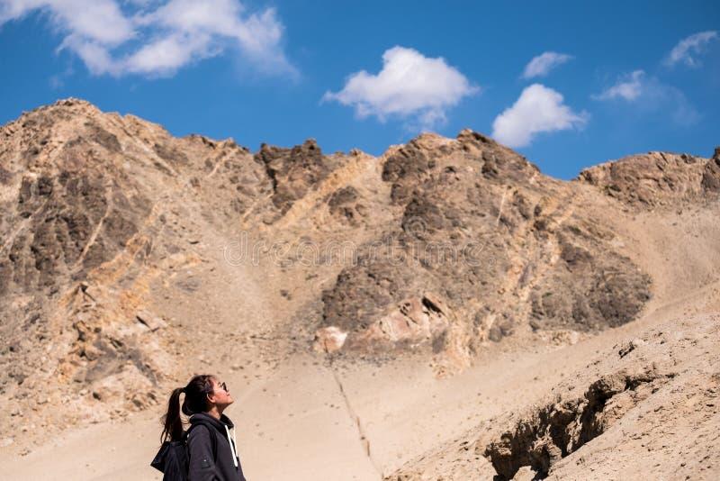 Ett turist- stående för härlig asiatisk kvinna framme av bakgrund för berg och för blå himmel royaltyfri bild