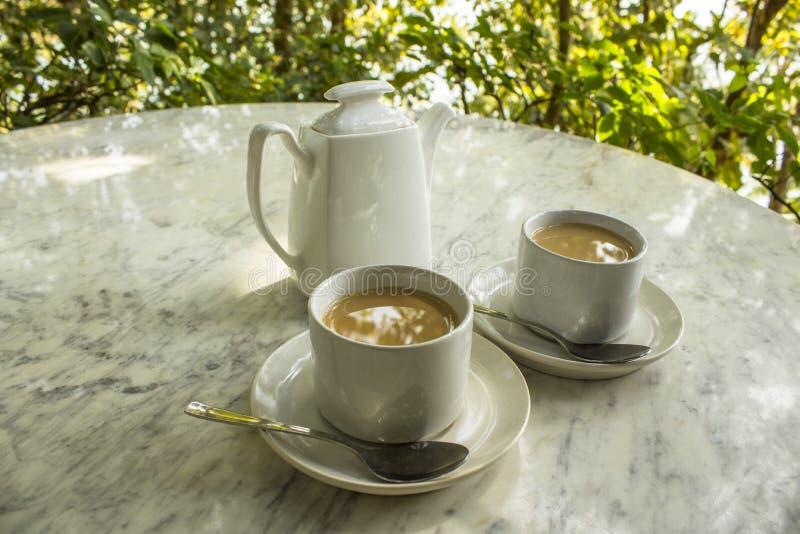 Ett två vitt keramiskt rånar med tefat, och skedar med mjölkar te, och en tekannaställning på marmorerar den ljusa tabellen mot e arkivbild