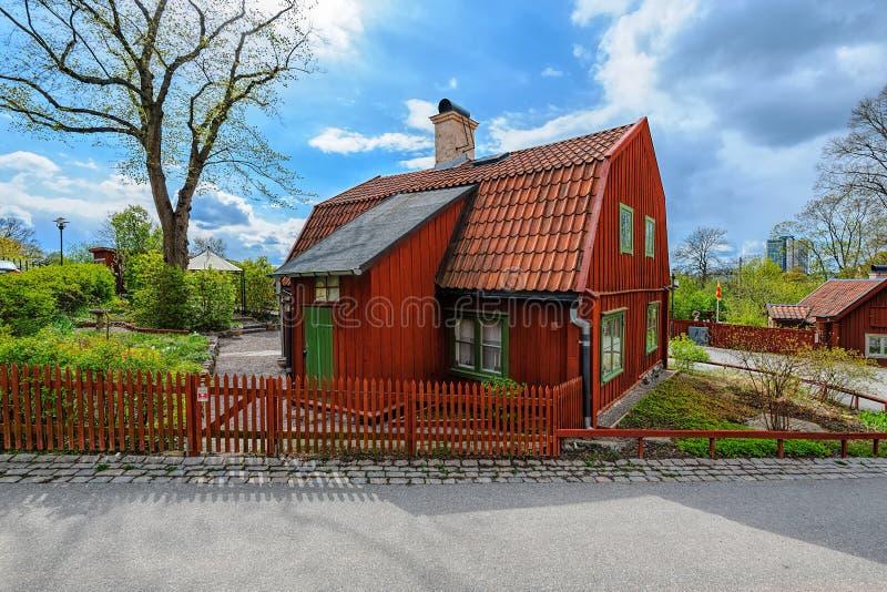 Ett typisk svenskt litet träbostads- hus som målas i traditionell falun som är röd i den kulturella sylten på Vita Bergen White arkivbild