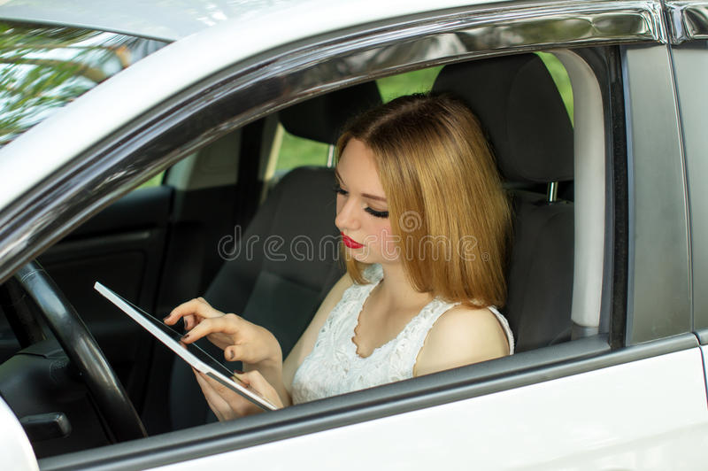 Ett ung flickaarbete, medan köra bilen arkivbild