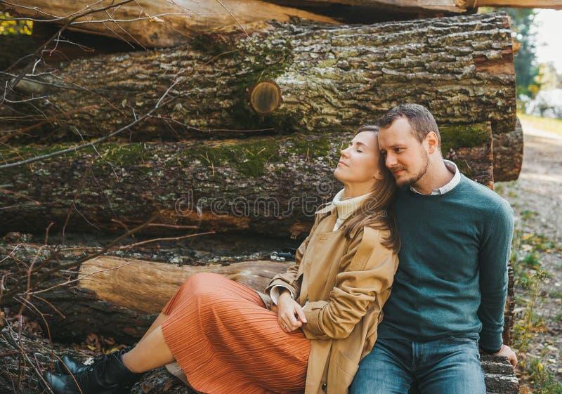 Ett ungande par som sitter på de avverkade stockarna i skogen. kärlekshistoria fotografering för bildbyråer