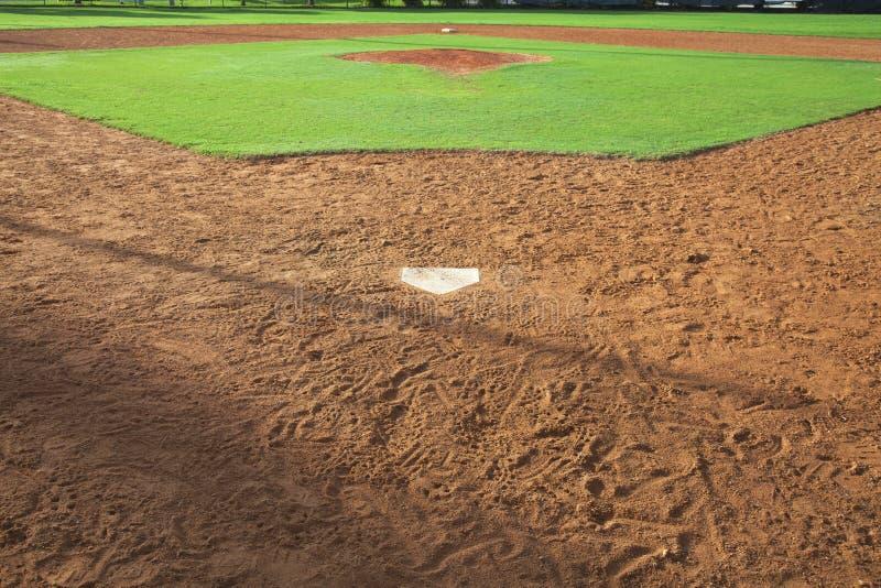 Ett ungdombaseballfält beskådade hemifrån plattan i morgonljus royaltyfri fotografi
