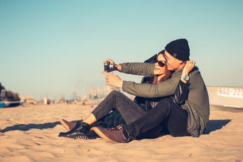 Ett ungt älska par spenderar rolig tid vid havet och gör selfies Mannen och kvinnan har vårkläder royaltyfria foton