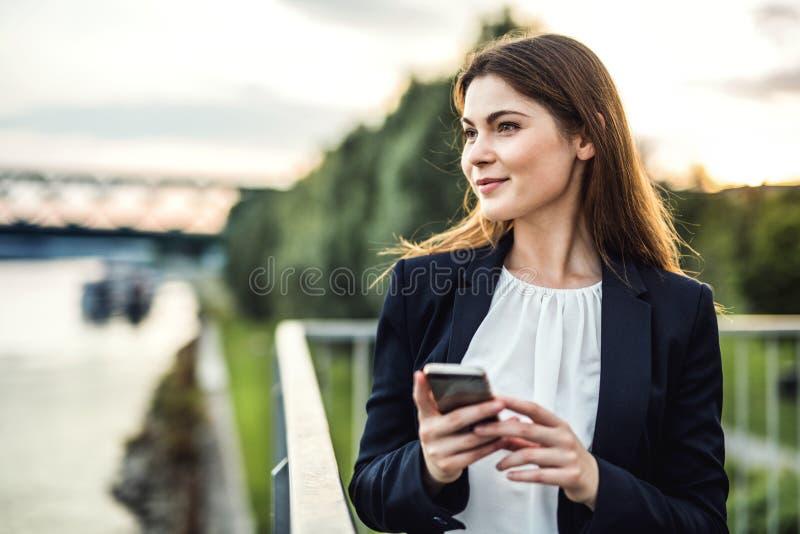 Ett ungt affärskvinnaanseende på flodbanken, genom att använda smartphonen arkivfoto