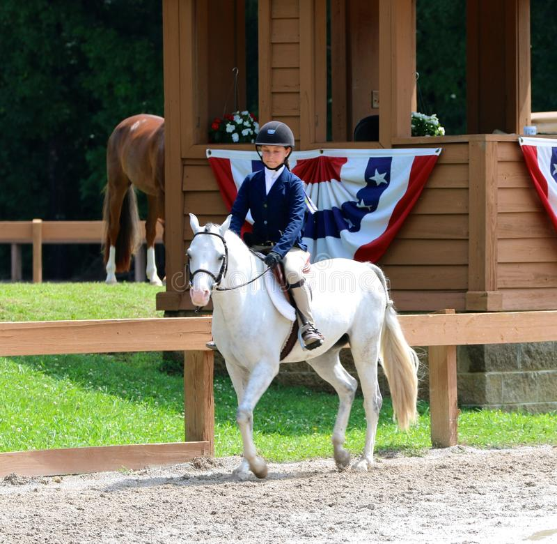 Ett ungt barn rider en häst i showen för den Germantown välgörenhethästen arkivbild