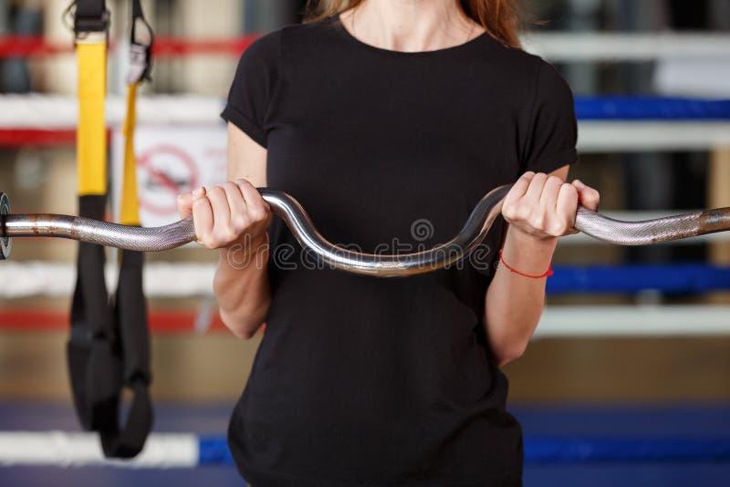 Ett ungt idrotts- gör bicepkrullning royaltyfri foto
