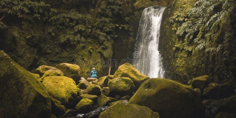 Ett ungt kvinnligt sammanträde under den lilla vattenfallet i den regniga skogen med slätade vattenströmmar och stenblock som täc arkivfoto