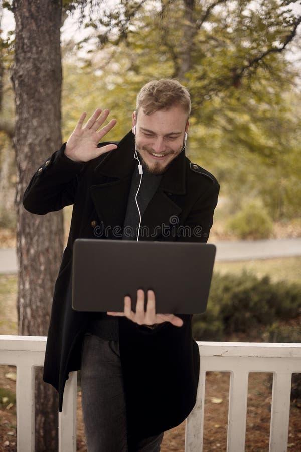 Ett ungt le och lycklig maninnehavb?rbar dator i handen som h?lsar n?gon som g?r en gest med en lyftt hand ?ver videokonferensen  royaltyfri bild