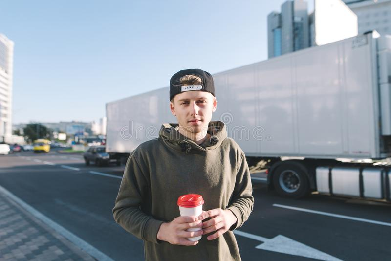 Ett ungt le pojkeanseende i gatan med kaffe i hans händer Studenten står på väg- och lastbilbakgrunden Lifestyl royaltyfri bild