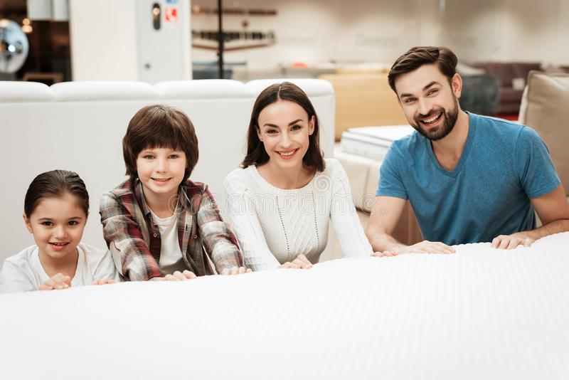 Ett ungt lyckligt familjsammanträde bak säng i ortopediskt madrasslager Provningssoftness av madrassen royaltyfri foto