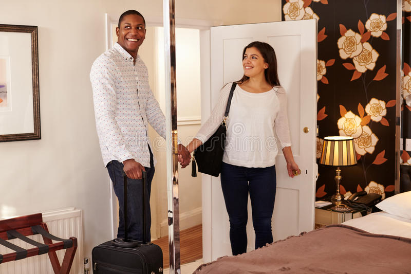 Ett ungt mång- etniskt par som ser deras hotellrum arkivbild