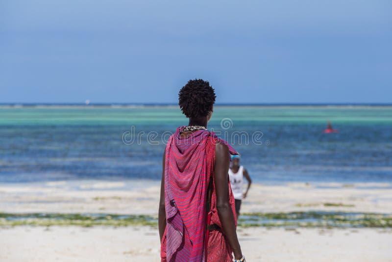 Ett ungt Maasai grabbanseende på stranden på bakgrund av blå himmel och havet royaltyfri fotografi
