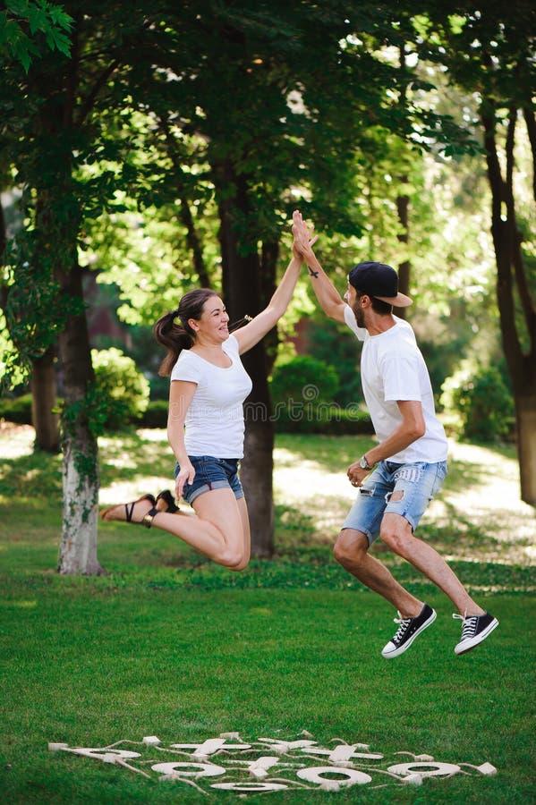 Ett ungt par firar segern som spelar muskelryckning-TAC-tån i, parkerar arkivbild