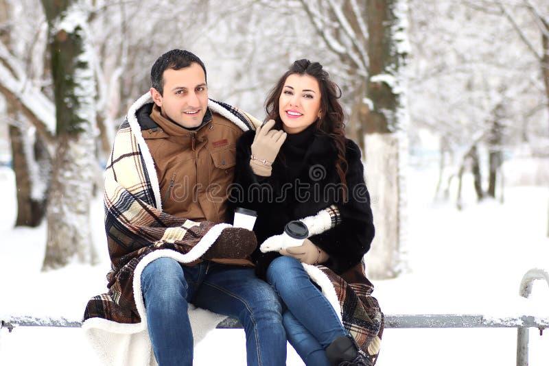 Ett ungt par går i en vinter parkerar arkivfoton
