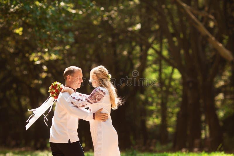 Ett ungt par i en traditionell ukrainsk bekläda whithbukett att tycka om den soliga dagen på Stryisky parkerar i Lviv royaltyfri foto