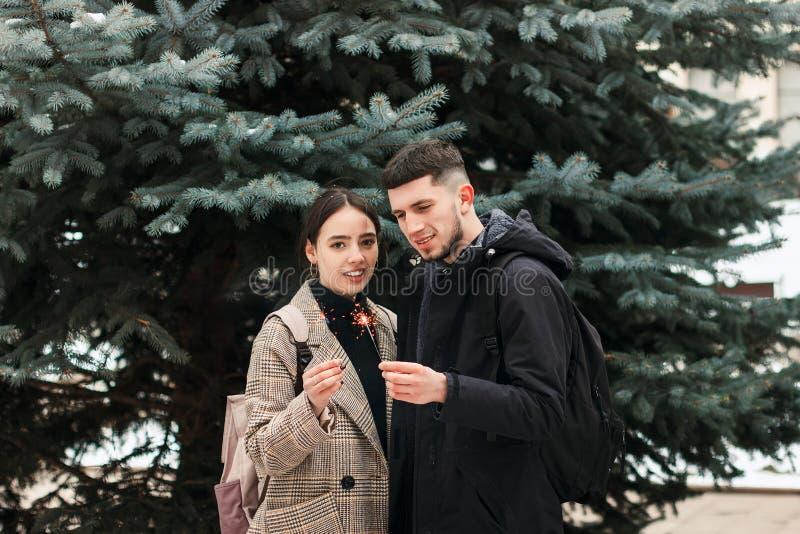Ett ungt par med tomtebloss i händerna i staden parkerar arkivfoto