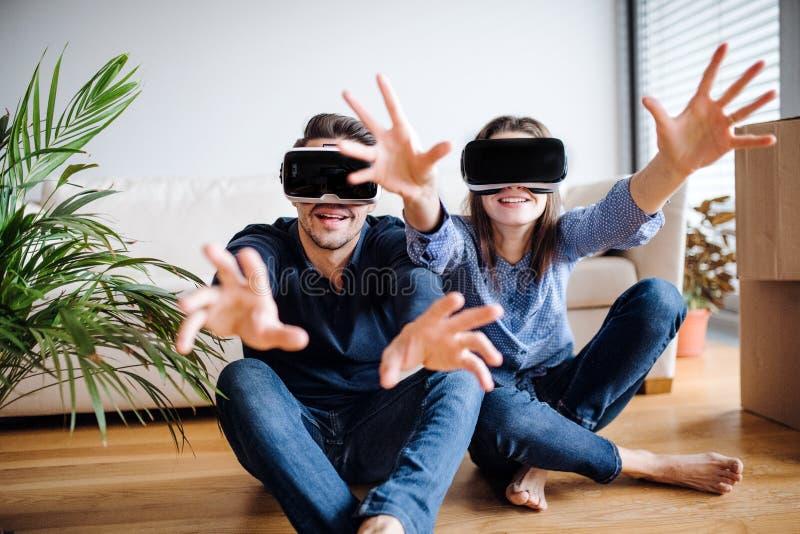Ett ungt par med VR-skyddsglasögon som sitter på ett golv, inflyttning ett nytt hem arkivfoton