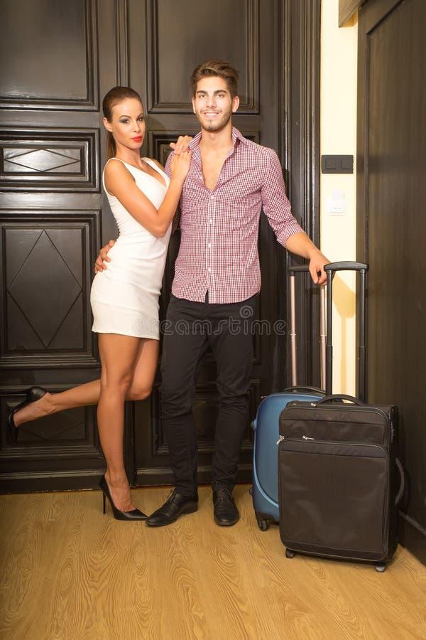 Ett ungt par som ankommer till deras hotellrum arkivfoton