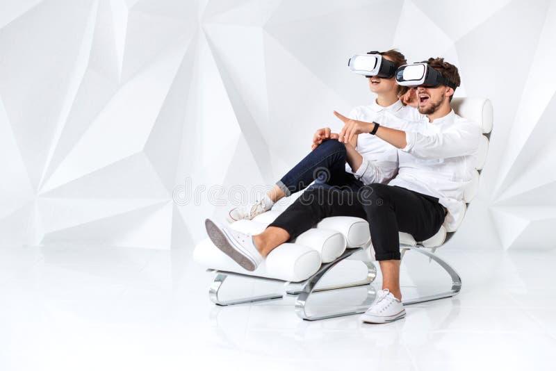Ett ungt par som bär VR-hörlurar med mikrofon som sitter på vit stol i ett rum med vita väggar och golv arkivbild