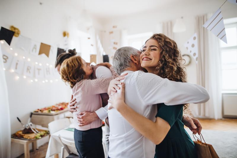Ett ungt par som hälsar föräldrar eller morföräldrar på det inomhus födelsedagpartiet arkivbild