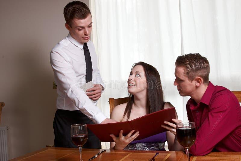 Ett ungt par som läser en meny fotografering för bildbyråer