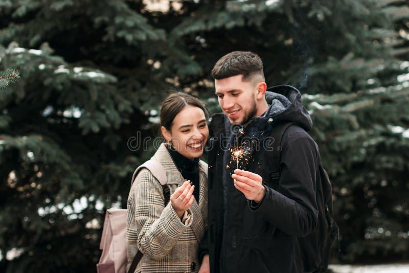 Ett ungt par som skrattar med Bengal ljus i händerna arkivfoto