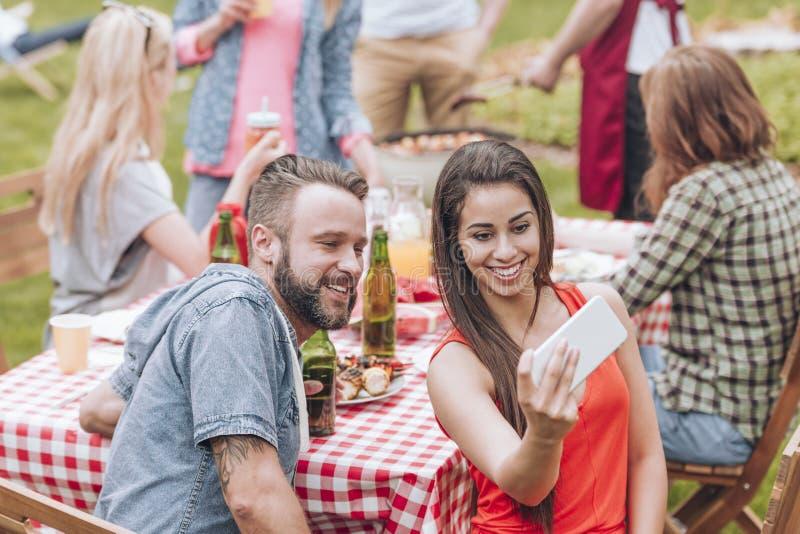 Ett ungt par som tar ett selfiefoto på en helgBBQ, festar outs arkivbild