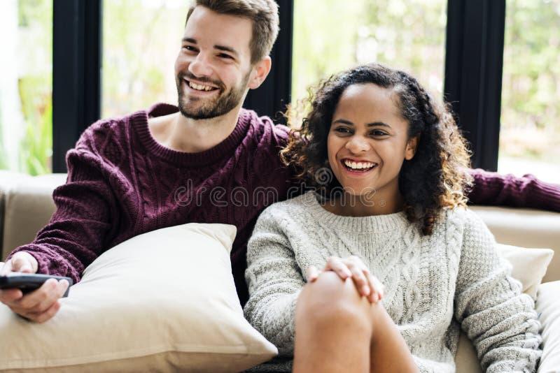 Ett ungt par som tillsammans håller ögonen på en TV-program royaltyfria foton