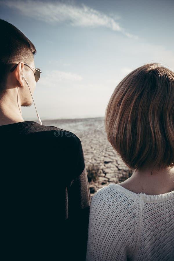 Ett ungt par, tonåringar som står sidan - förbi - sid i hörlurarli royaltyfria bilder