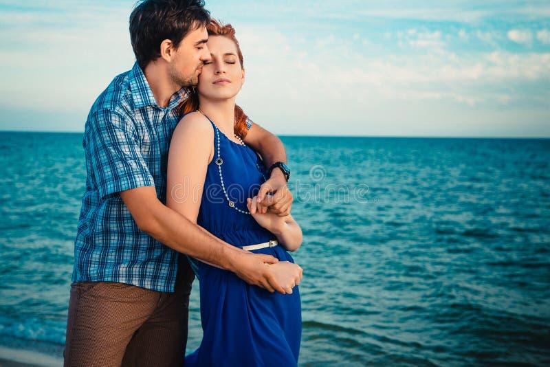 Ett ungt par tycker om en sen eftermiddag för mitt- sommar, på en våta san fotografering för bildbyråer