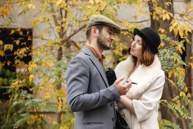 Ett ungt retro par Gangstergrabben röker en cigarr, och flickan ser honom som är förälskad utomhus fotografering för bildbyråer