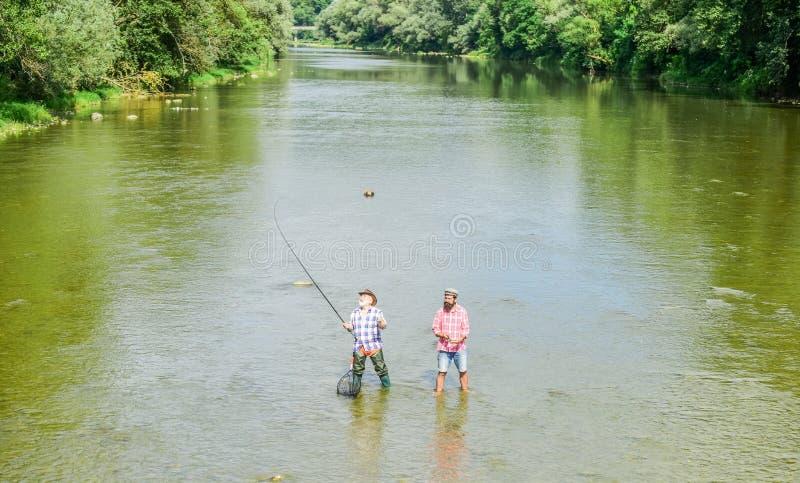Ett uppdrag. Stort modigt fiske. Manligt kamratskap. Fader- och Sonfiske. advent. två glada fiskare med fiskstav royaltyfri bild
