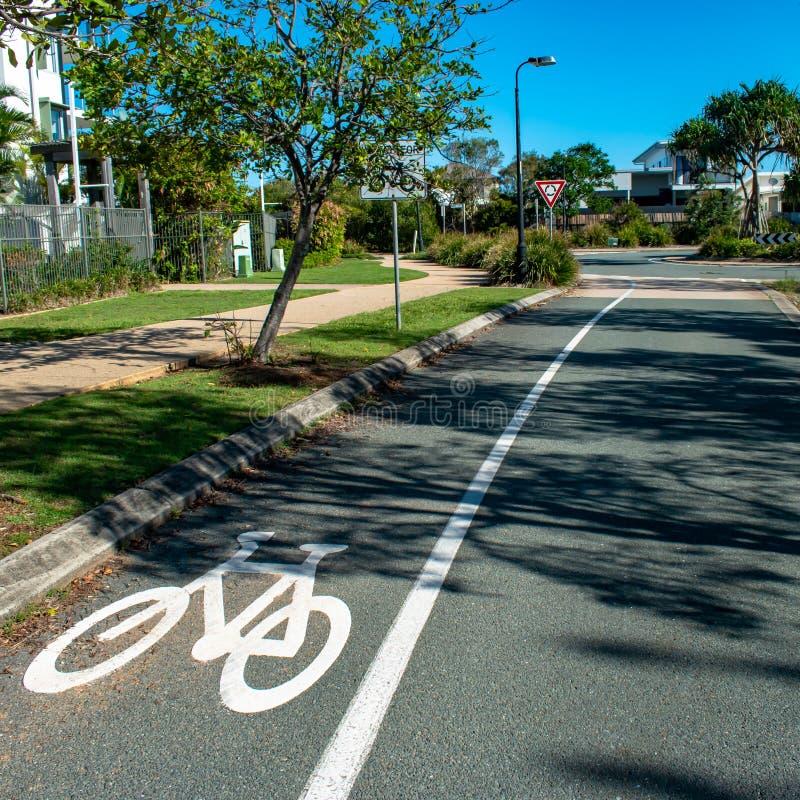 Ett vägmärke som döljas av ett bevuxet träd arkivfoto