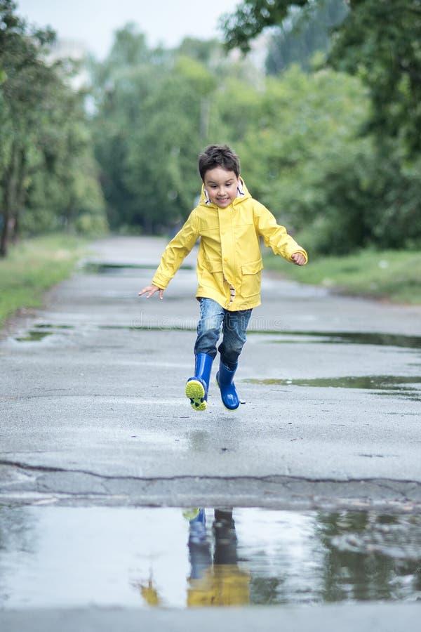 Ett vått barn hoppar i en pöl gyckel på gatan Blanda i sommar arkivbilder