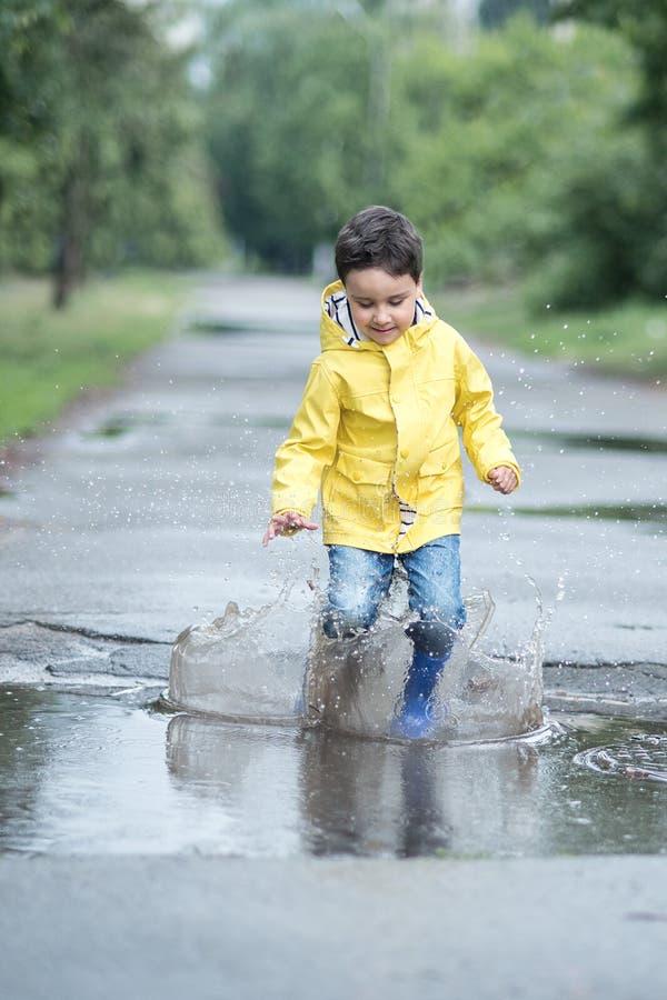 Ett vått barn hoppar i en pöl gyckel på gatan Blanda i sommar fotografering för bildbyråer