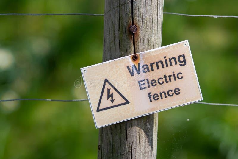 Ett varnande folk för krokigt tecken att ett elektriskt staket är närvarande Tecknet fästas till ett trådstaket med en grön arkivbild