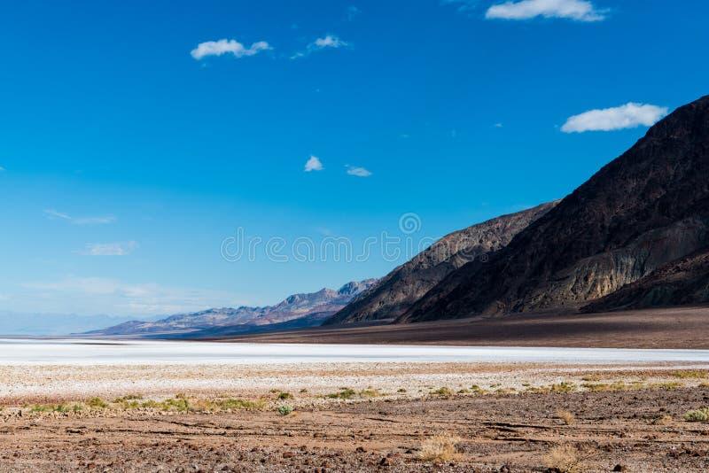 Ett vidsträckt kargt ökenlandskap av saltar lägenheter med en bergskedja som går tillbaka in i avståndet under en blå himmel med  royaltyfri fotografi