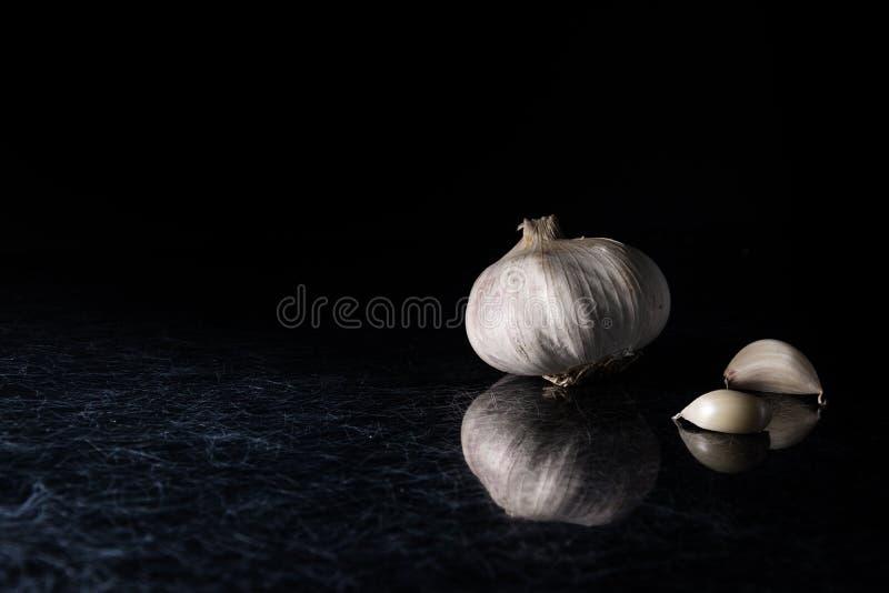 Ett vitlökhuvud med vitlökkryddnejlikor på en svart och silverkök överträffar bakgrund fotografering för bildbyråer