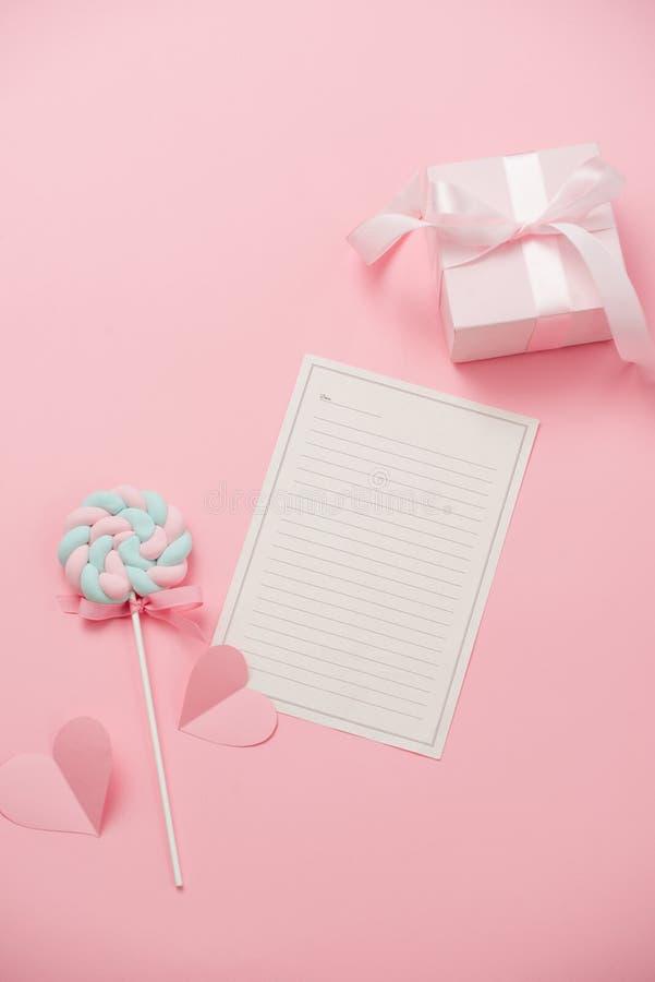 Ett vitt ark av papper för meddelandet till älskad, godis på rosa bakgrund Lyckligt kvinnas dagbegrepp Åtlöje upp royaltyfri bild