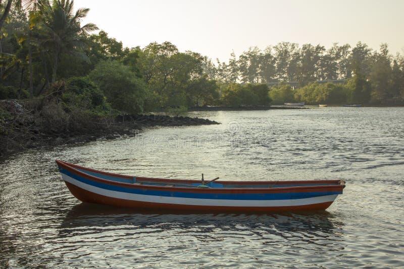 Ett vitt blått rött tomt träfartyg på vattnet på kusten royaltyfri bild