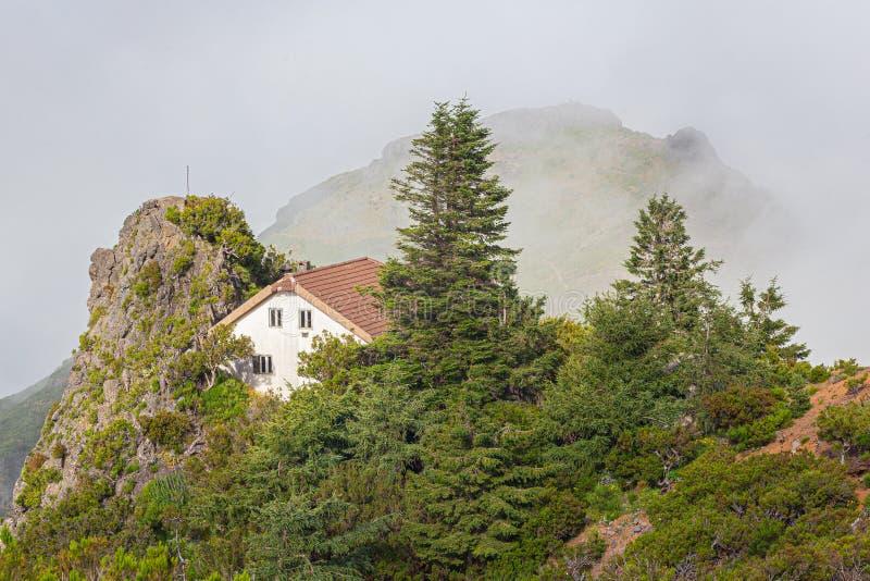 Ett vitt hus med ett tak i bergen bland molnen arkivfoton