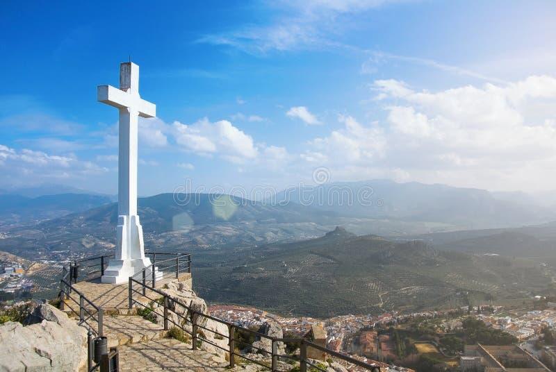 Ett vitt korsar över den Jaen staden på berget, ett symbol av staden med toppiga bergskedjan Magina berg på bakgrund på solig dag royaltyfri fotografi