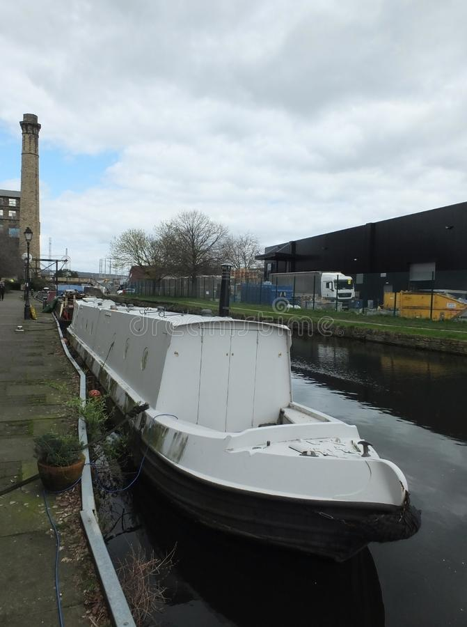 Ett vitt smalt fartyg förtöjde på kanalen i en industriområde av huddersfield med maler och överbryggar arkivfoto