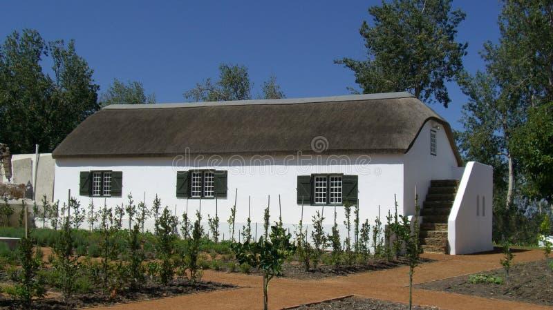 Ett vitt washsommarhus med vasstaket royaltyfri foto