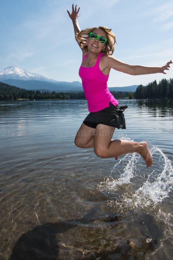 Ett vuxet kvinnligt hoppar i en sjö som plaskar vatten bak hennes fot på en sommardag i Kalifornien, nära monteringen Shasta royaltyfri foto