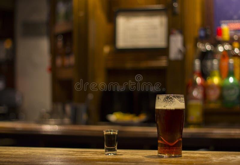 Ett whiskyskott och ett exponeringsglas av engelskt öl på den London baren royaltyfri fotografi