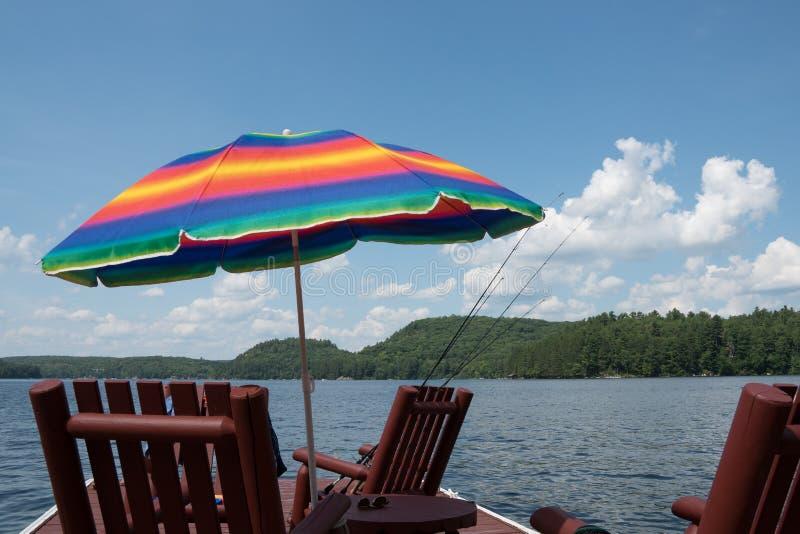Ettfärgat parasollparaply på en lakesideskeppsdocka arkivbilder