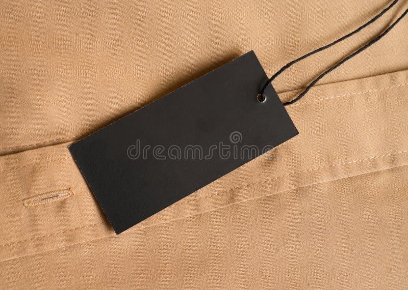 Etykietki metki czarny mockup na beżowej koszula fotografia stock