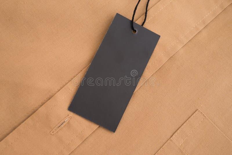 Etykietki metki mockup na beżowej koszula zdjęcia stock
